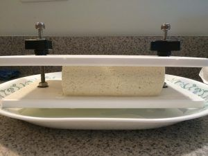 tofu being pressed before marinating in sauce