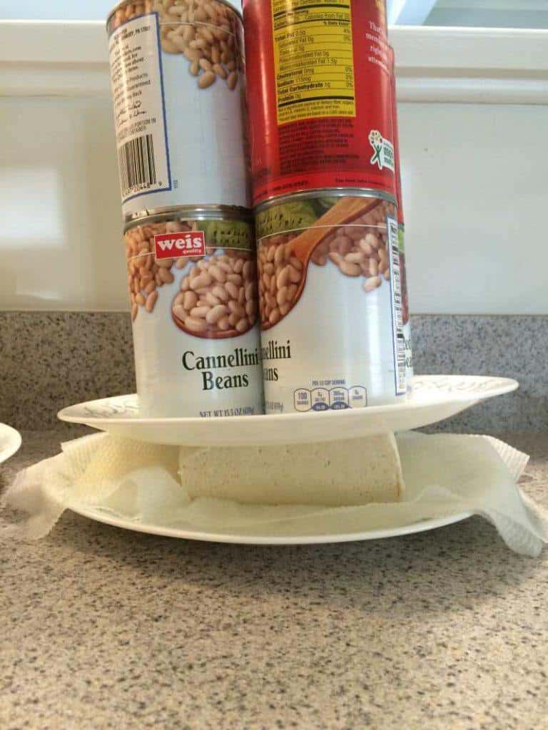using cans to drain the water from the tofu