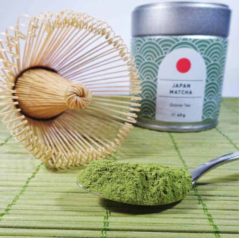 picture of matcha powder with a matcha whisk