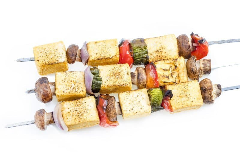 Grilled tofu mushroom kebab on skewer served on plate.