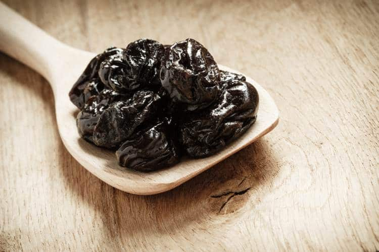 prunes on a wooden spoon