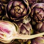 Pile of Purple artichokes ready for cooking. One artichoke is cut