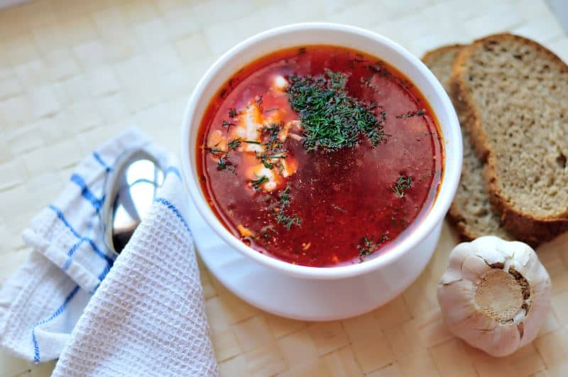 borscht in a bowl with bread on the side