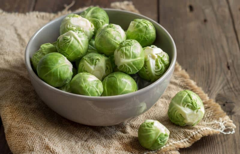 Brussels sprouts in a bowl on an old wooden table