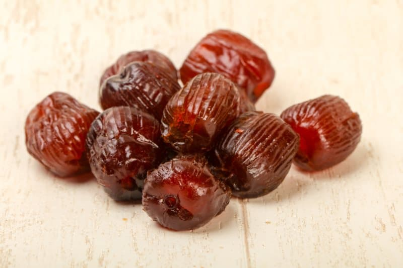 ripe dates sitting on a wood surface
