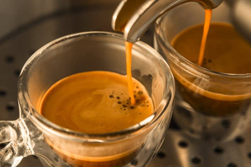 espresso coming out of the machine into two cups double shot
