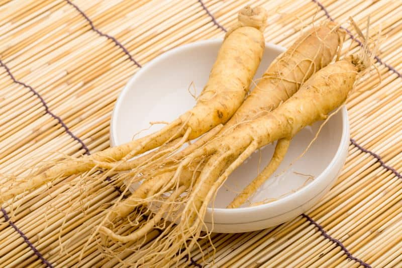 Ginseng in a bowl on a wooden background