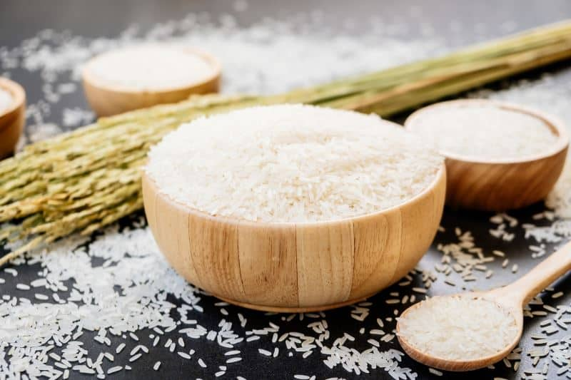 Raw Jasmine rice in wooden bowl  and spoon with grain and seed