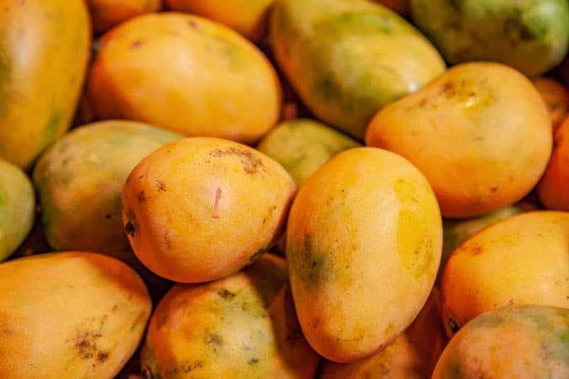 a bunch of mangoes in a pile