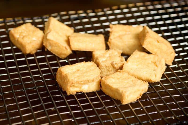 Stinky tofu on a metal oil screen