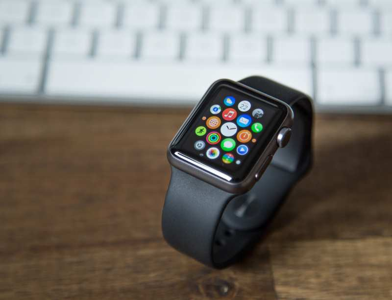 apple watch with vegan band on table next to computer