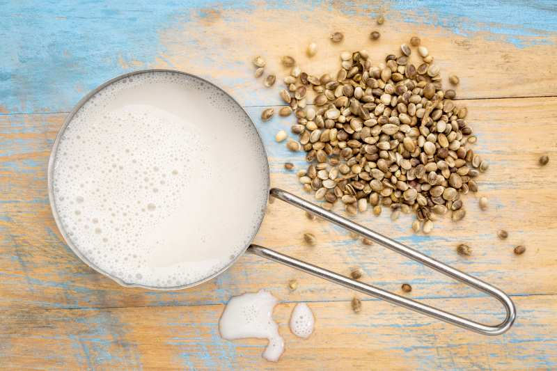 hemp milk in a measuring cup and hemp hearts on a table