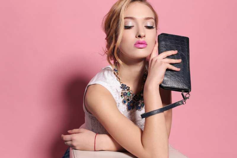 stylish woman holding vegan wristlet wallet