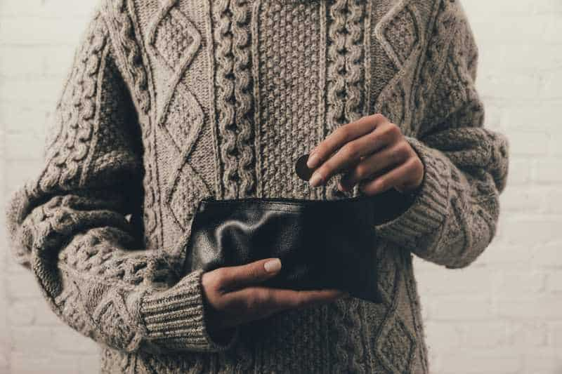 woman putting change into a vegan wallet with coin pocket