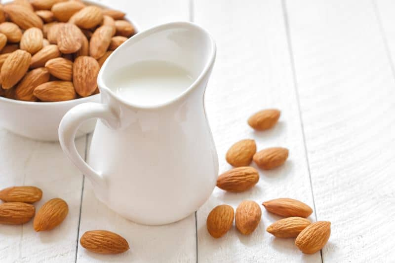 Almond milk on a table with fresh almonds