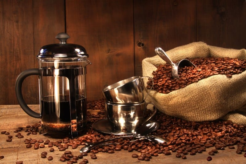 Sack of coffee beans with french press coffee and cups