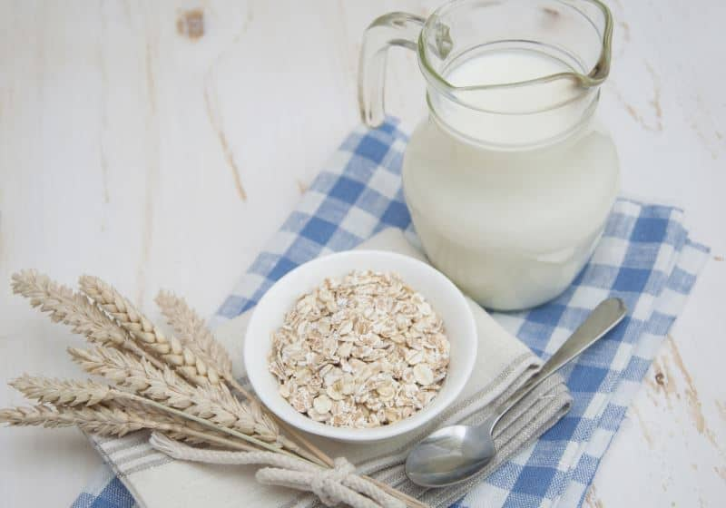 Oat Milk on a table with towel and spoon