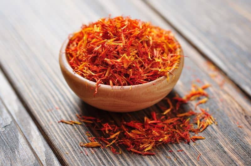 Saffron in wooden bowl on wooden background