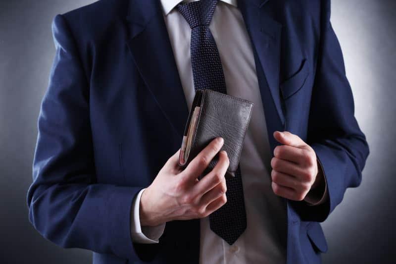 man putting away vegan wallet in coat