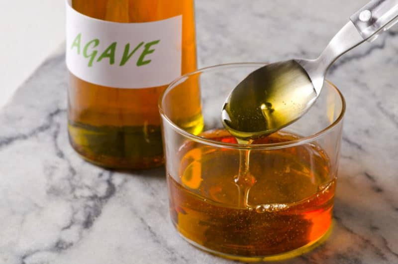 Agave nectar pouring from a spoon into a glass with a bottle of agave syrup in the background.