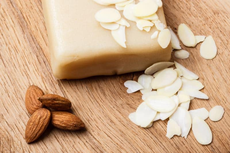 A block of almond paste with whole and sliced almonds on a wooden surface.