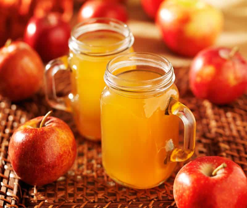 Apple cider in mason jars surrounded by apples.