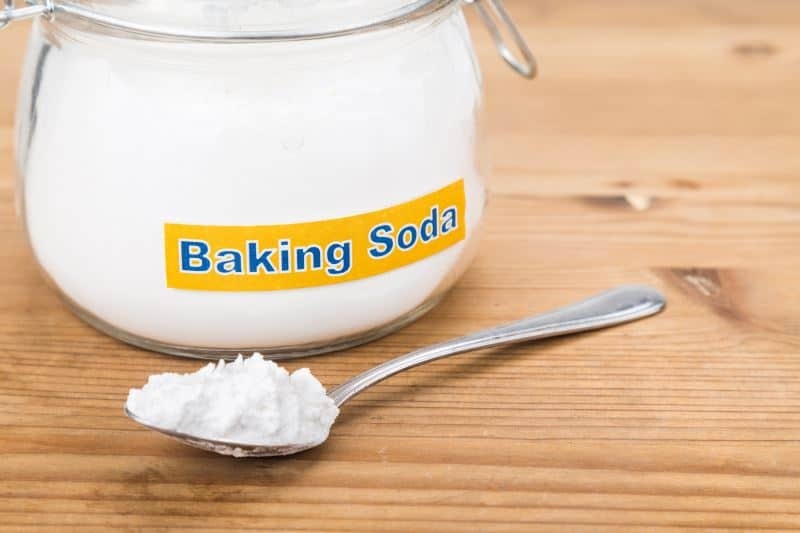 A labeled jar of baking soda behind a spoon with baking soda on it.