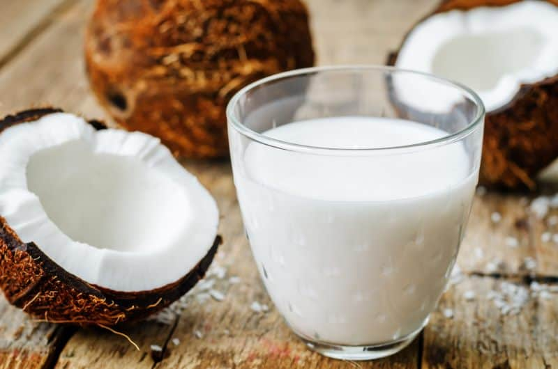 A glass of coconut milk next to coconuts on a wooden table.