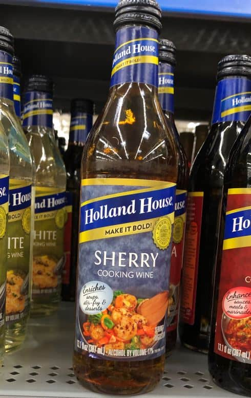 A bottle of Holland House Sherry Cooking Wine on a supermarket shelf.