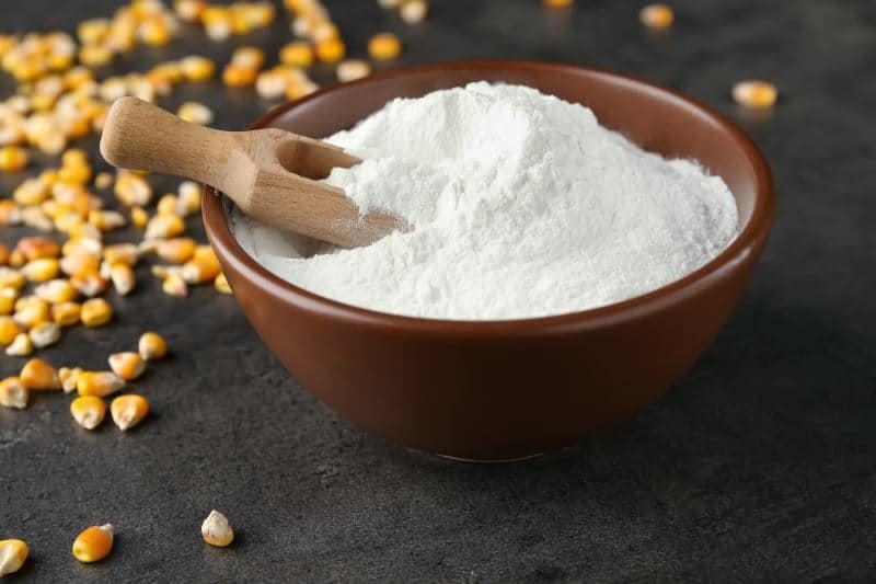 Cornstarch in a bowl with a wooden scoop.