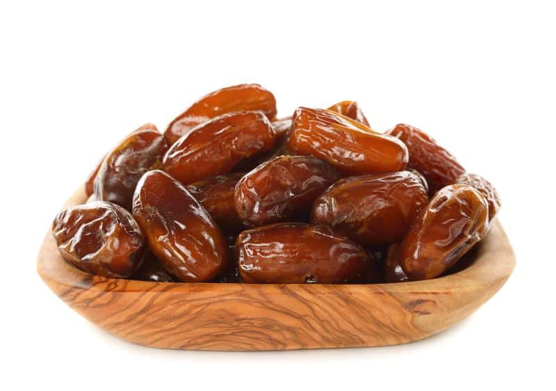 Dried dates in a wooden dish against a white background.