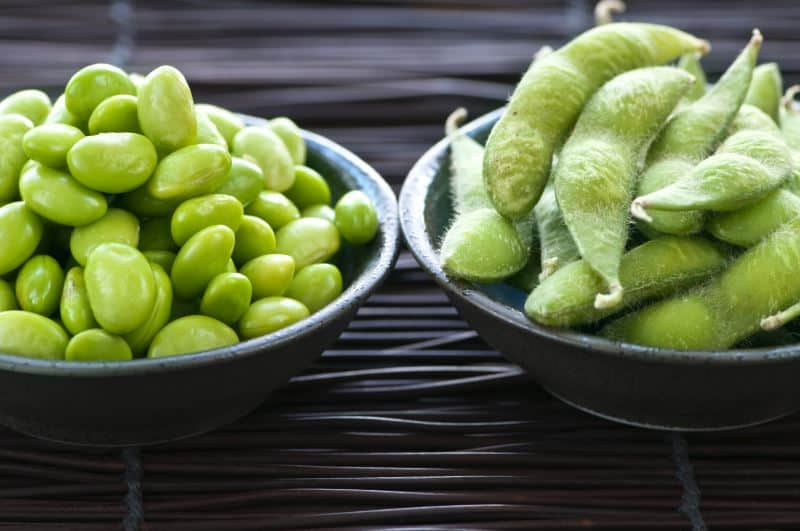 Edamame shelled and in pods in two bowls side by side.