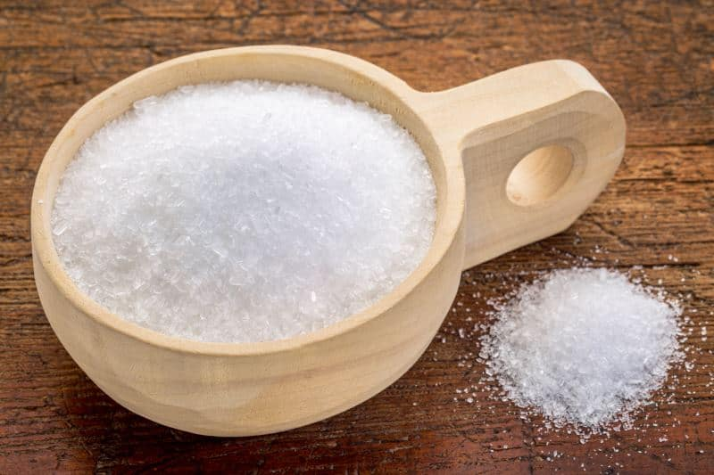 Epsom salt in a wooden cup on a wood surface.
