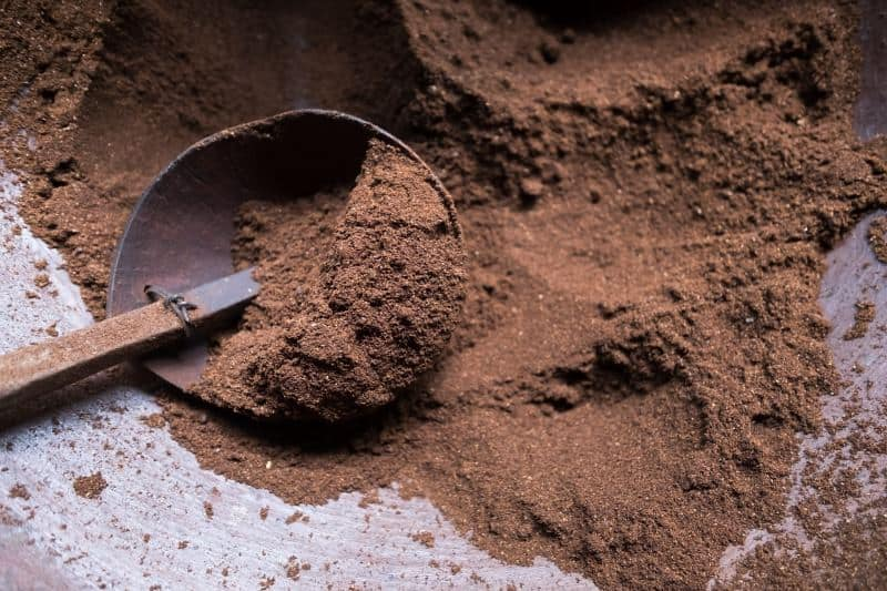 A heap of finely ground espresso powder with a rustic spoon.