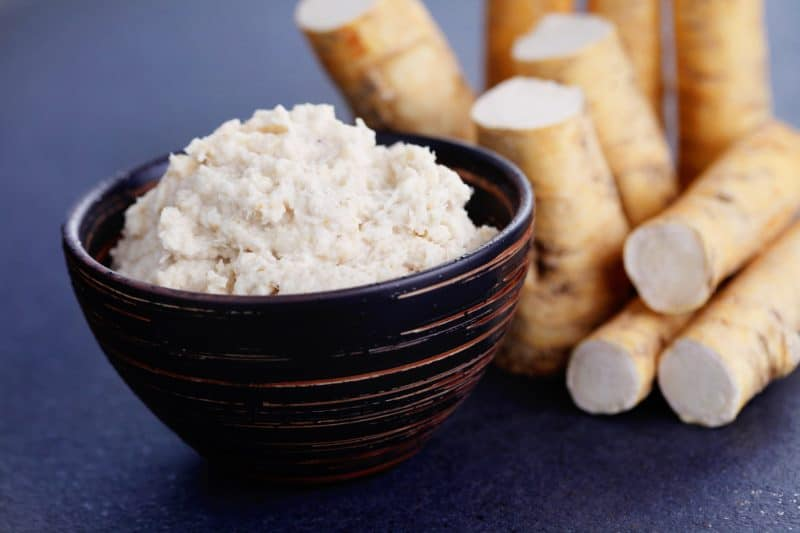 Prepared horseradish in a bowl next to fresh horseradish roots.