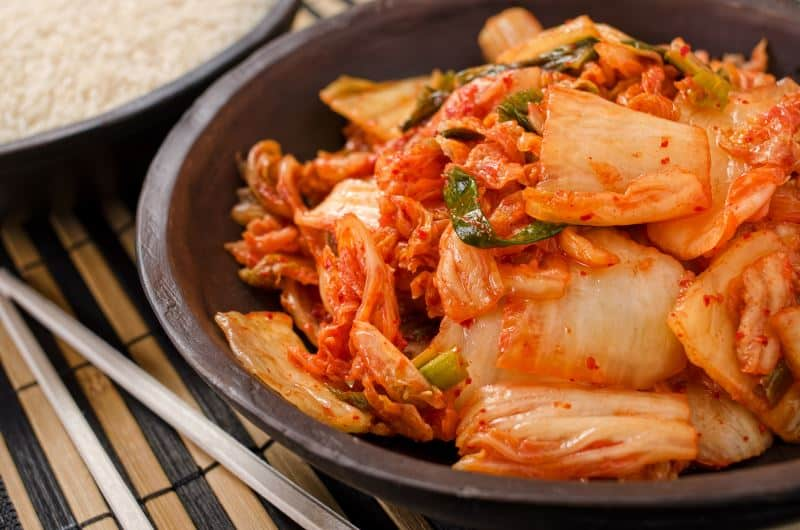 Kimchi in a bowl next to chopsticks and white rice.