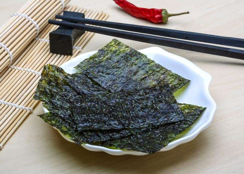 Nori sheets on a plate with chopsticks and a wooden mat.