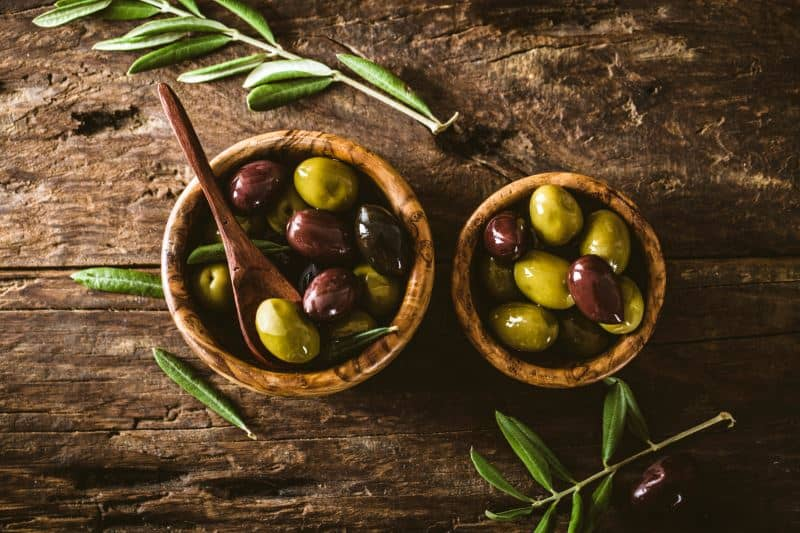 Mixed green and Kalamata olives in bowls on a rustic table with olive leaves.