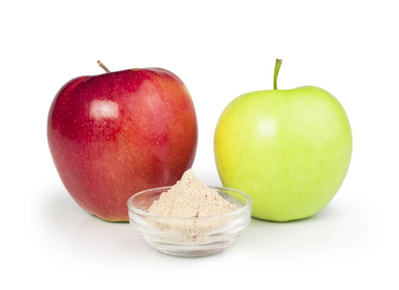 A dish of pectin powder in front of two apples against a white background.