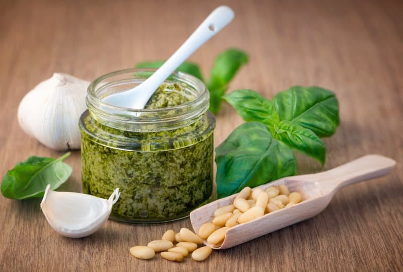 Basil pesto in a jar with a white spoon, pine nuts, garlic and basil leaves.
