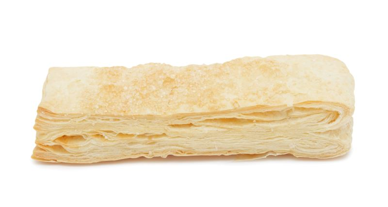 A sheet of baked puff pastry against a white background.
