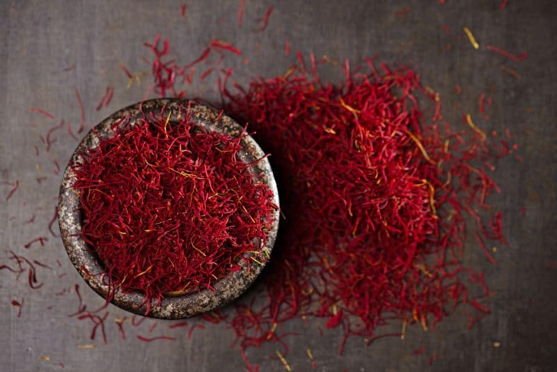 Saffron spice threads in a metal dish surrounded by scattered saffron threads.