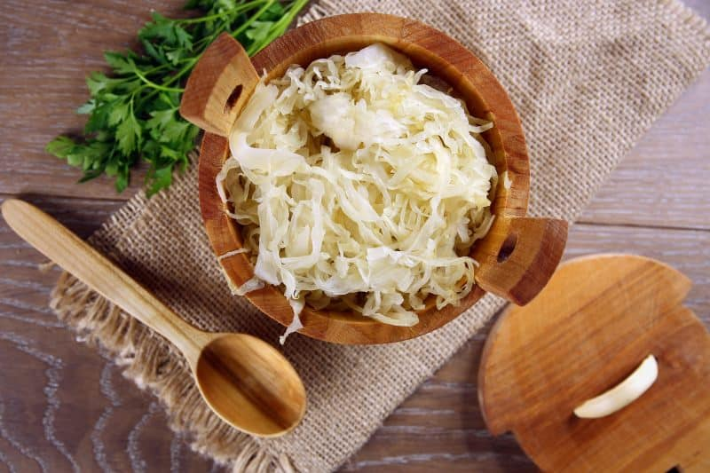 Sauerkraut in a wooden barrel on a wood table.