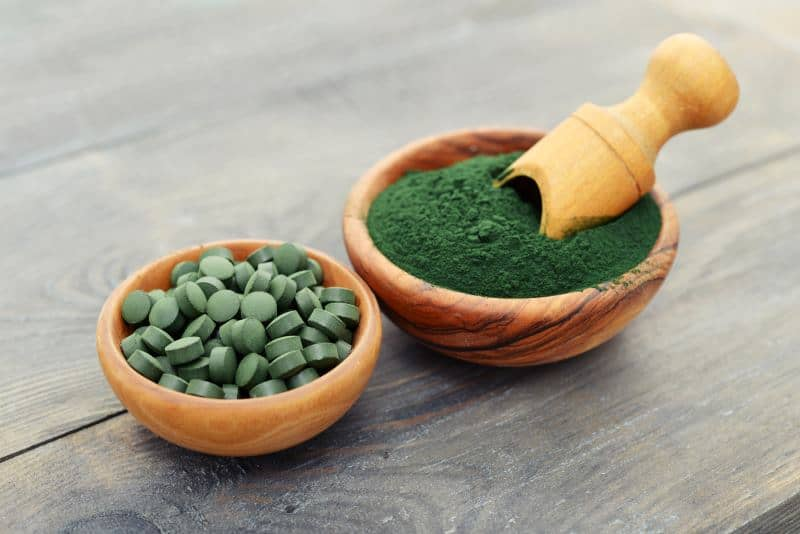 Spirulina tablets and powder in wooden bowls.