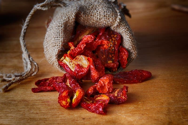 Sun dried tomatoes in a burlap sack on a wooden counter.