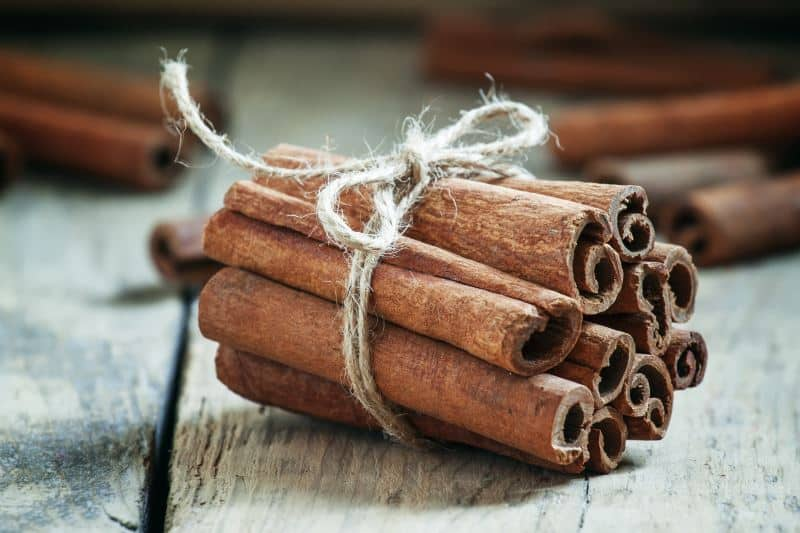 A bundle of cinnamon sticks tied with jute twine on a wooden table.