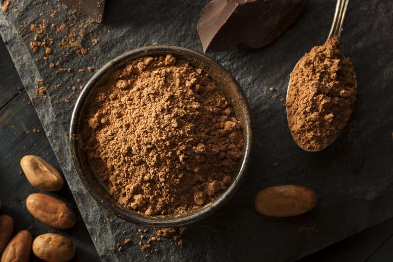 A bowl of cocoa powder next to cacao beans and broken pieces of chocolate on a stone table