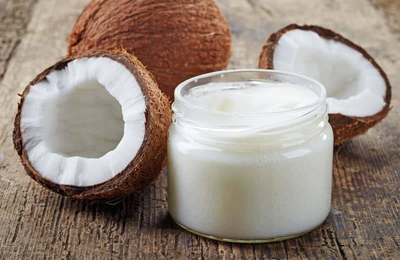 A jar of coconut oil surrounded by fresh coconuts on a wooden table.