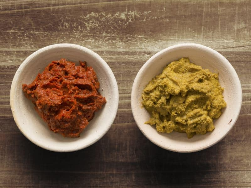 Red and green curry paste in bowls on a wooden counter.