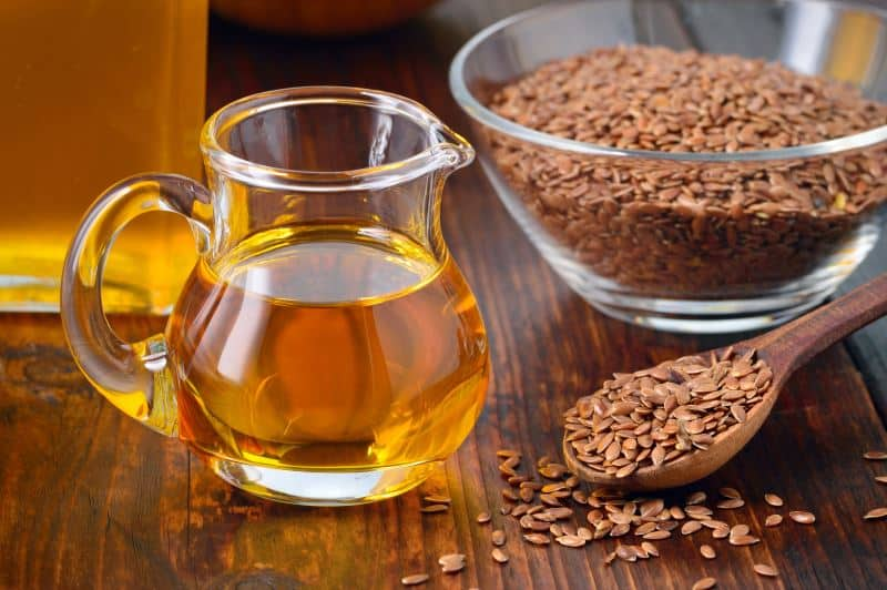 A pitcher of flaxseed oil next to whole flaxseeds in a glass bowl and wooden spoon.